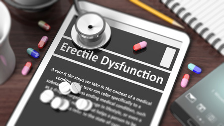 erectile: Tablet with Erectile Dysfunction on screen, stethoscope, pills and objects on wooden desktop.