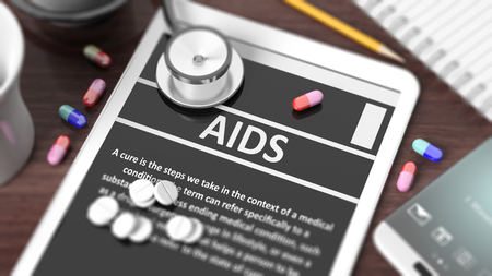 sexually transmitted disease: Tablet with AIDS on screen, stethoscope, pills and objects on wooden desktop. Stock Photo