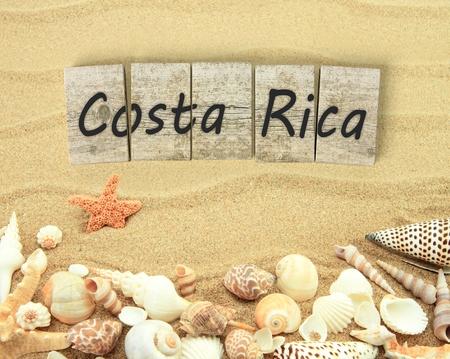 arena: Costa Rica en piezas de tablero de madera con conchas de mar y arena Foto de archivo