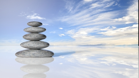 stack rock: Zen stones stack from large to small  in water reflecting peaceful sky with clouds. Stock Photo