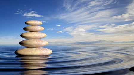 Zen stones stack from large to small  in water with circular waves and peaceful sky. Standard-Bild