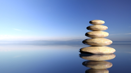 Zen stones stack from large to small  in water with blue sky and peaceful landscape background.