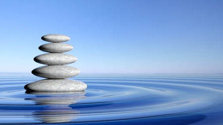 rocks water: Zen stones stack from large to small  in water with circular waves and blue sky.
