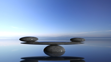Balancing Zen stones in water with blue sky and peaceful landscape. Stock Photo