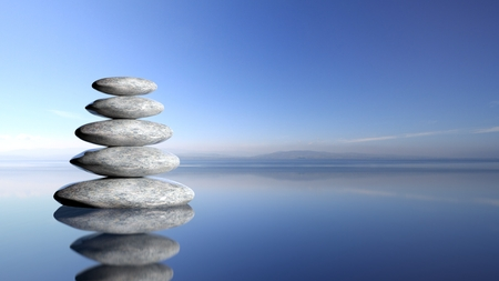 zen: Zen stones stack from large to small  in water with blue sky and peaceful landscape background.