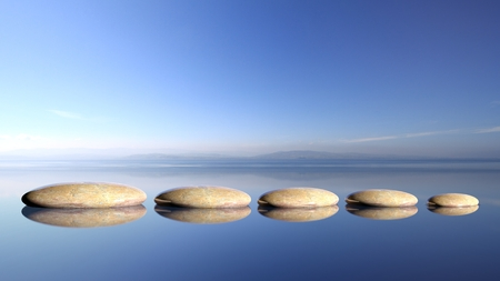 zen rocks: Zen stones row from large to small  in water with blue sky and peaceful landscape background.