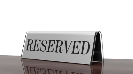 reserved seat: Glossy reservation sign on wooden surface, isolated on white background. Stock Photo