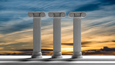 Three ancient pillars with sunset sky background. Stock Photo