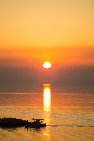 dominating: Sun disk reflecting on sea surface, with orange color dominating the seascape