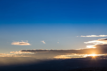 troposphere: Sunset with orange and blue sky above ground, aerial shot.
