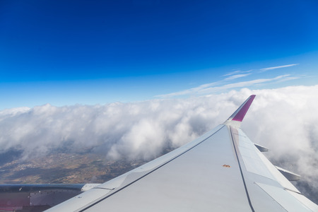 troposphere: Blue horizon and white clouds. Aerial shot with airplane wing Stock Photo