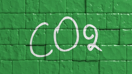 CO2 emissions: Green painted brick wall with CO2 text graffiti Stock Photo