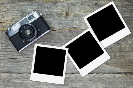 analog camera: Old analog camera with blank photo frames, on wooden surface Stock Photo
