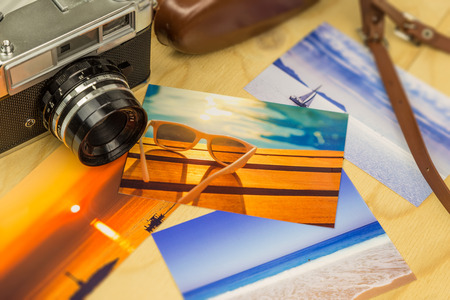 analog camera: Old analog camera with colorful summertime pictures, on wooden surface Stock Photo