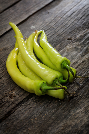 wooden surface: Stack of green chili peppers, on wooden surface