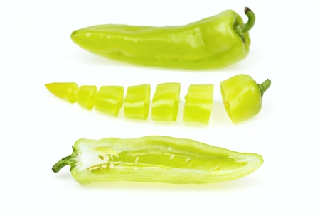 pointy: Three pointy green pepper, one half and one cut into pieces, on white background. Stock Photo