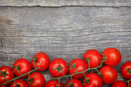wooden surface: Bunches of red cherry tomatoes, on wooden surface with copy-space