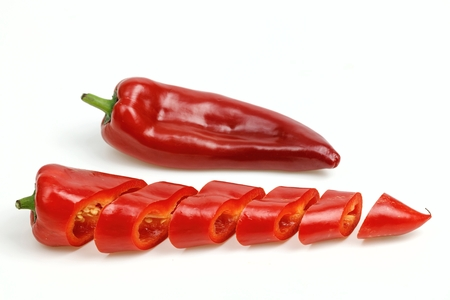 pointy: Pointy red pepper and one cut into pieces, on white background.