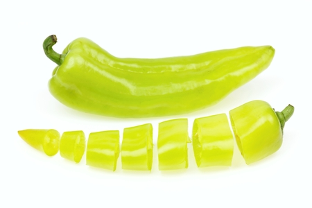 pointy: Pointy green pepper and one cut into pieces, on white background. Stock Photo