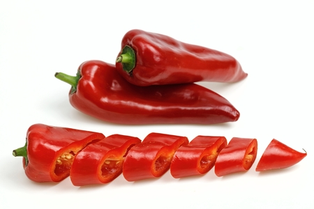 pointy: Pointy red peppers and one cut into pieces, on white background.
