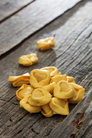 tortellini: Uncooked tortellini set on wooden surface