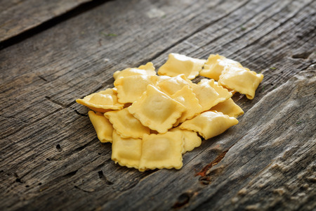 uncooked: Uncooked ravioli set on wooden surface