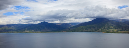 water  panoramic: Panoramic view on still water against of mountains under white clouds