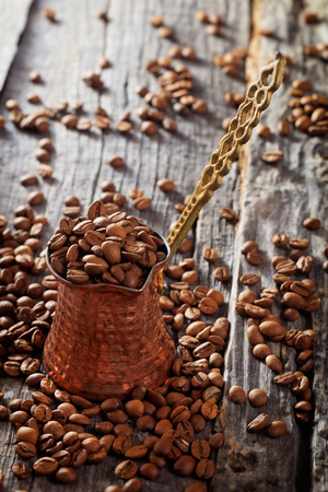 cezve: Scattered raw coffee beans with metal Turkish cezve on wooden table