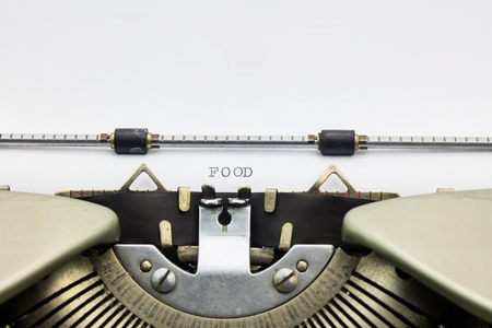 printing machine: Close-up of food word in capital letters on white sheet in printing machine Stock Photo
