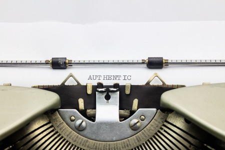 Close-up of word Authentic on typewriter sheet