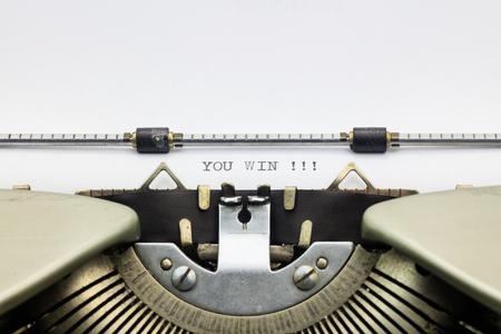 printed: Close-up of words You win on typewriter sheet