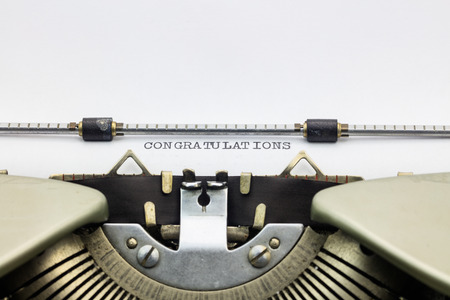 machinery space: Close-up of congratulations word in capital letters on white paper in typewriter