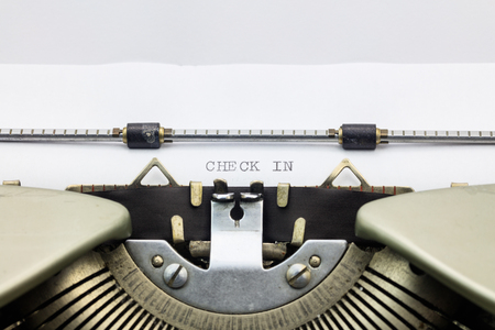 check in: Close-up of words Check In on typewriter sheet Stock Photo