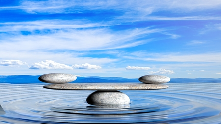 3D rendering of balancing Zen stones in water with blue sky and peaceful landscape. Archivio Fotografico