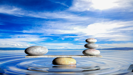 feng: 3D rendering of balancing Zen stones in water with blue sky and peaceful landscape. Stock Photo