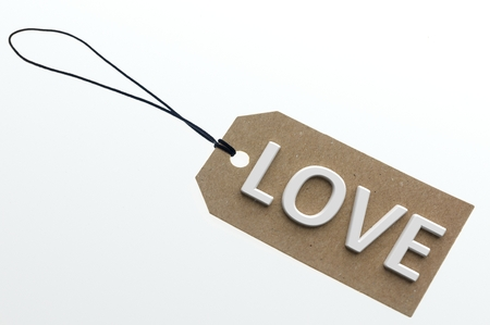 pasteboard: LOVE word on cardboard tag on white background.Isolated