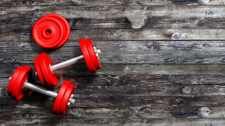 adjustable dumbbell: 3D rendering of adjustable metallic red dumbbells, on wooden background with copy-space