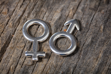 men and women: Closeup of two metallic gender symbols, on wooden background. Stock Photo