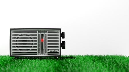 transistor: transistor de radio antigua en la hierba, sobre fondo blanco con espacio de copia. representación 3D