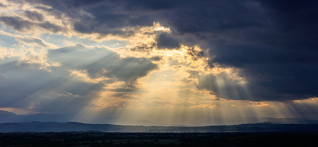 sky sun: Stormy clouds with radiating sunbeams above countryside. Stock Photo