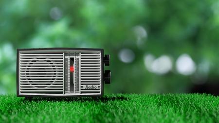 transitor: transistor de radio antigua en la hierba verde y el fondo verde bokeh. representaci�n 3D