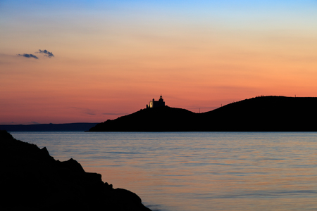 pink sunset: View on water surface and mountain silhouette with lighthouse at pink sunset