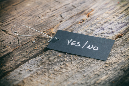 affirmative: Closeup of pricing tag with twine and YesNo text on wooden background