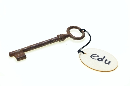 A wooden tag with edu text on old rusty key, isolated on white background