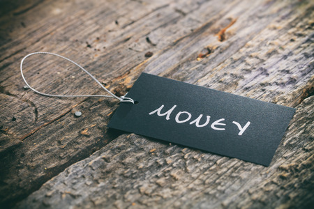 transfer pricing: Closeup of pricing tag with twine and Money text on wooden background