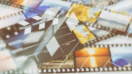 entertainment equipment: Clapperboard on filmstrips with pictures abstract background Stock Photo