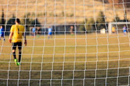 arquero de futbol: Goalkeeper through a football goal net