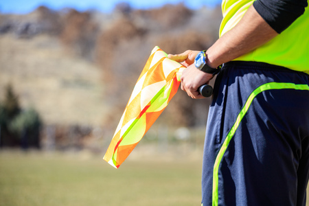 Football assistant referee with a flag