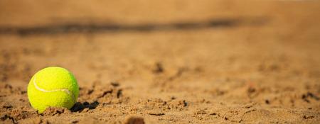 Tennisbal op een zandstrand - kopieer ruimte