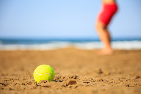 Tennis ball on a sandy beach - copy space Stock fotó